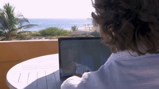 Handsome man working on spreadsheet on laptop computer at home with ocean view dolly shot