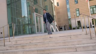 Handsome millennial businessman dancing down steps celebrating achievement and success in slow motion outside his office building wide shot