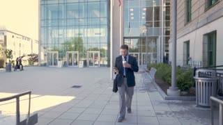 Handsome millennial businessman walking away from office building with an American flag using mobile phone technology and drinking to go coffee in slow motion stabilized shot