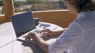 Handsome self employed entrepreneur man working on laptop from home office beach house with ocean view
