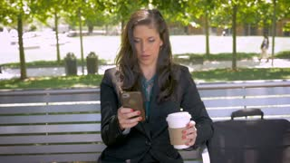 Happy attractive businesswoman sitting on park bench smiling and drinking coffee on smart phone reading emails or social networking push in slow motion