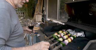 Happy attractive elderly senior man in his 70s drinking red wine and grilling vegetable kebabs on a bbq in his backyard