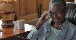 Happy, beautiful black senior woman in her 50s or 60s smiling and taking off her glasses while sitting on her living room sofa while looking at the camera