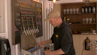 Happy brewmaster bartender filling a growler with beer at a small craft brewery or brew pub