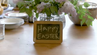 Happy Easter written on a small chalk board against a vase of pretty flowers on a wooden table as part of a Easter brunch- push in