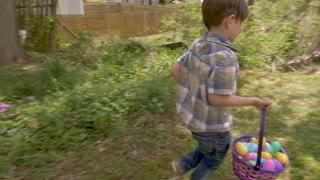 Happy excited young 4 - 5 year old cute boy holding a basket filled with easter eggs while walking outside in a backyard on a easter egg hunt in slow motion
