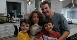 Happy family of four looking at the camera smiling and holding a friendly dog that is licking faces of the mom and son