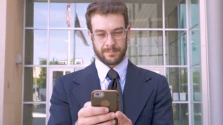 Happy handsome businessman with beard using smart phone app technology and smiling in slow motion outside of modern office building with American flag reflection