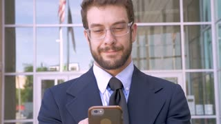 Happy handsome millennial man with beard and smart phone technology app looks at camera and smiles in slow motion close up shot