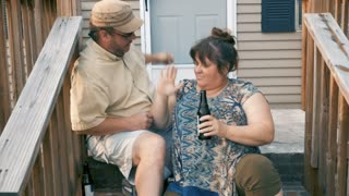 Happy large successful couple in their 30s or 40s high five while sitting on their front steps in front of their home in slow motion