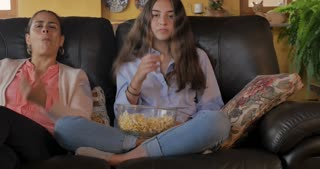 Happy Latino mother and teen daughter watching tv and eating popcorn together - dolly shot