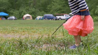 Happy little girl playing in the grass outside at a festival music event with a stick in slow motion
