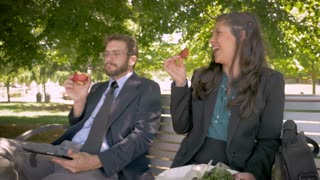 Happy male and female millennial business coworkers smiling and dancing while eating healthy food with digital tablet touchscreen technology in slow motion outside on a park bench