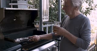 Happy man in his 40s puts his arm around an older senior adult man in his 70s while he is cooking potatoes wrapped in aluminum foil on a bbq grill