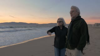Happy mature 60s couple pointing and smiling along upscale beachfront at sunset. Retired fit mature caucasian man and woman enjoying vacation exploring coast at dusk