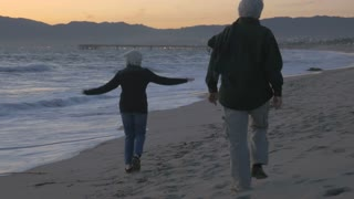 Happy mature 60s couple running and playing along upscale beachfront at sunset. Retired fit elderly caucasian man and woman enjoying vacation exploring coast at dusk