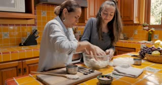 Happy Mexican woman and teenager girl kneading bread dough together - push in gimbal shot
