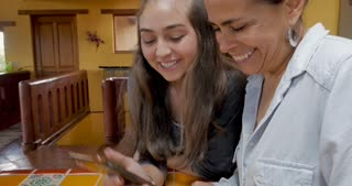 Happy mother and teenager daughter looking at a mobile phone smiling and laughing together - gimbal shot