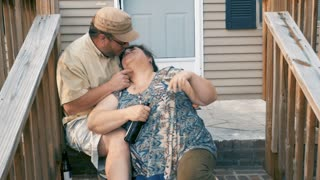 Happy plus sized couple in their 30s or 40s kissing and embracing while sitting on their front steps in slow motion