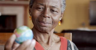 Happy smiling African American mature woman over 50 looking a world globe for places to travel