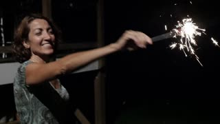Happy smiling attractive mixed ethnic woman in her 40s waiving a sparkler at night celebrating a holiday such as 4th of July Independence Day in slow motion