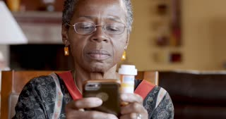 Happy smiling black woman over 50 refilling her medication prescription drugs online using smart phone technology app in her home