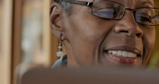 Happy smiling elderly senior black woman age 50 - 60 reading good news on her laptop or tablet display - dolly shot