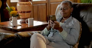 Happy smiling elderly senior black woman in her 50s or 60s using her smart phone at home