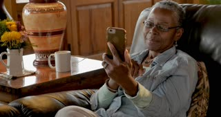 Happy smiling elderly senior black woman in her 50s or 60s video chatting on her mobile phone app technology
