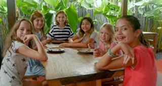 Happy, smiling group of multi ethnic young girls sitting at a table giving the thumbs up and looking at the camera