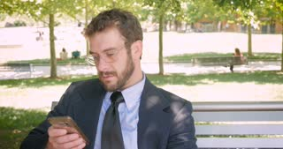 Happy smiling handsome business man with beard and eyeglasses reading emails or social media posts on smart phone dolly shot in 4k