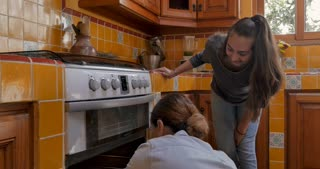 Happy smiling latino mother removing cookies from an oven with her teenager daughter in their kitchen - close up gimbal shot