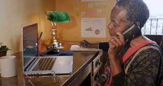 Happy smiling mature black woman talking and hanging up her cordless phone at home office - dolly shot
