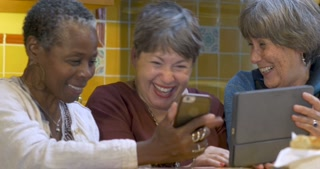 Happy smiling mixed racial group of friends over 60 laughing and sharing tablet and smart phone technology together