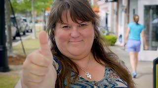 Happy smiling plus sized woman gives the thumbs up outside endorsing something to the camera