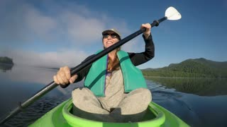 Happy smiling woman in her 40s or 50s paddling a kayak in a mountain lake having fun