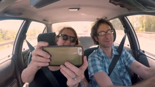 Happy smiling woman taking selfies of herself and her male driver friend in a car during the day