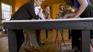 Happy successful young mostly women attractive entrepreneurs discussing building business blueprints in slowmo crane shot