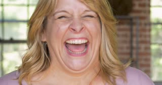 Happy woman laughing out loud lol cracking up and being hysterical at something funny
