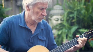 Healthy active fit baby boomer man concentrating on playing acoustic guitar outdoors in his garden in the summer