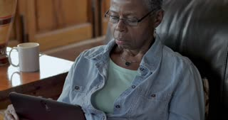 Healthy black baby boomer senior woman in her 60s using a digital tablet on her living room sofa in her home during the day - close up dolly shot