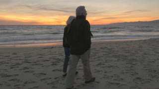 Healthy elderly 60s couple walking and exercising on beach at sunset. Retired fit mature caucasian man and woman enjoying vacation exploring coast at dusk