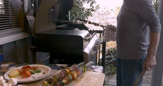 Healthy elderly senior man in his 70s removing cooked vegetable shish kebabs from the barbecue