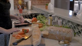 Healthy, fit woman making a sandwich for lunch with healthy fresh vegetables, cold cuts, meats, and sliced bread - slow motion dolly shot