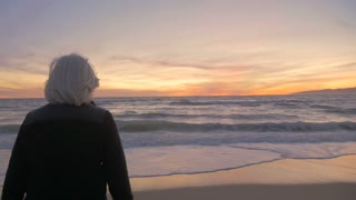 Healthy retired 60s mature active woman looking at a beautiful sunset on beach