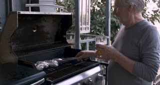Healthy vibrant senior citizen man in his 70s holding a craft beer in a pint glass and cooking potatoes wrapped in aluminum foil on a bbq