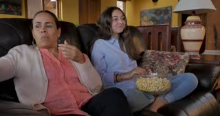 Hispanic mom turning on tv with remote and getting surprised and laughing with teenage daughter