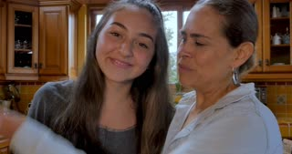 Hispanic Mother and teenage daughter kiss, smile, and look at the camera in their kitchen