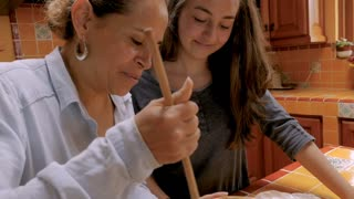 Hispanic mother and teenager daughter look at each other smiling while cooking together - slow motion