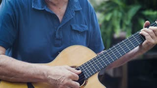 Hobby senior baby boomer classical guitar player performing on his acoustic guitar outside tilt up